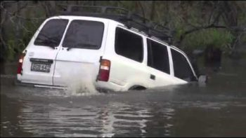 SUV Drives Through Flooded Creek
