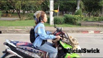 Bird Flies Along With Woman Biker In Thailand