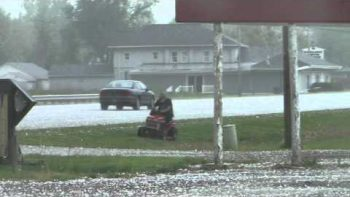 Man Mowing Lawn During Crazy Hail Storm