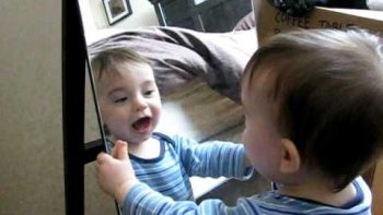 Baby Looking At His Tongue In Mirror